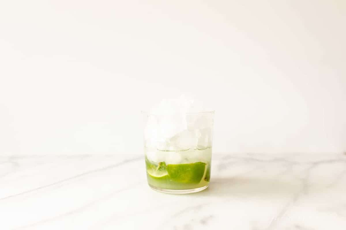 muddled lime mint and rum in a glass filled with ice