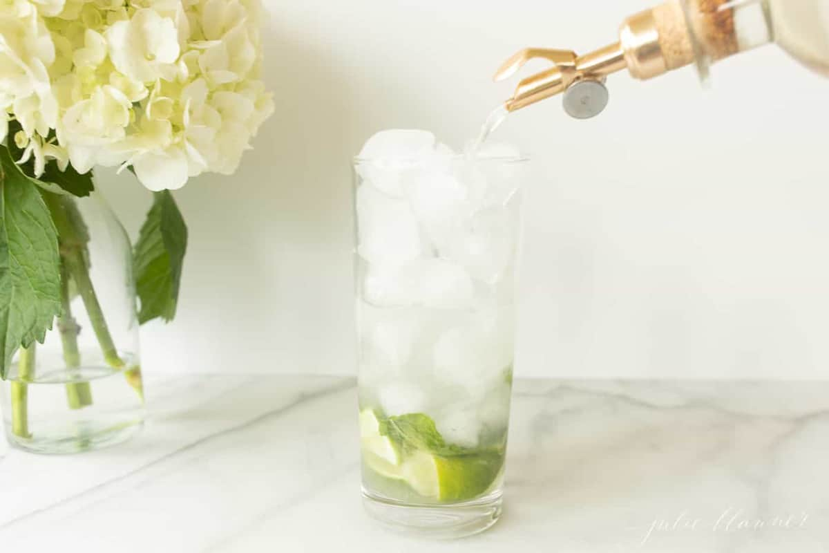pouring simple syrup over lime mint and vodka