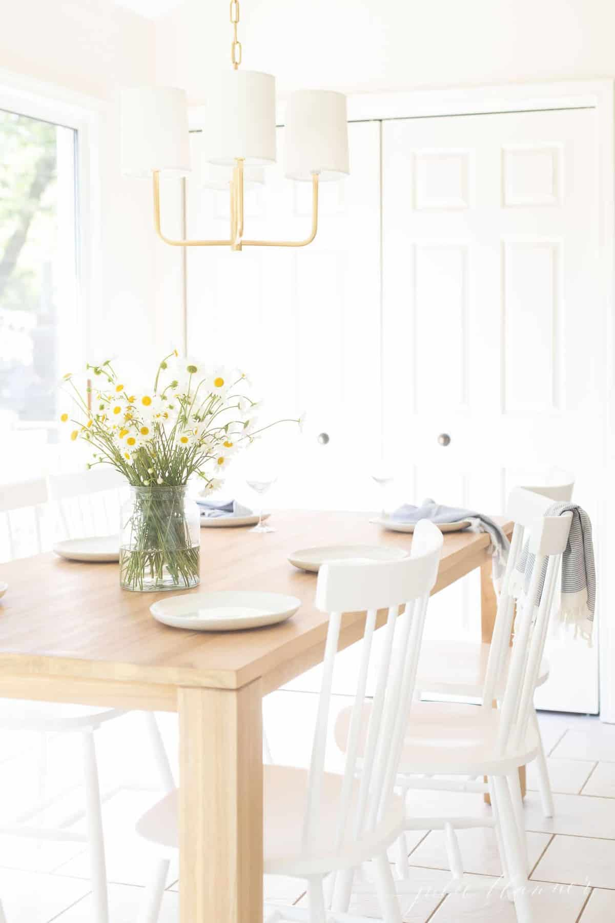 brass light over teak table with white chairs