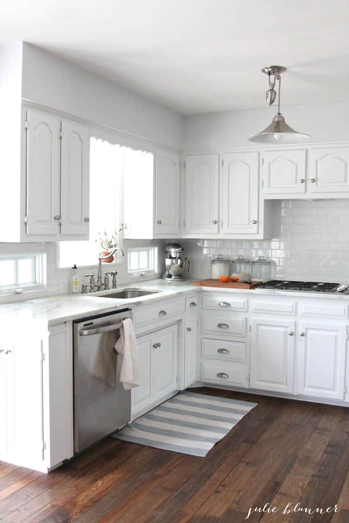 nickel pulley light in grey and white kitchen with wood floors