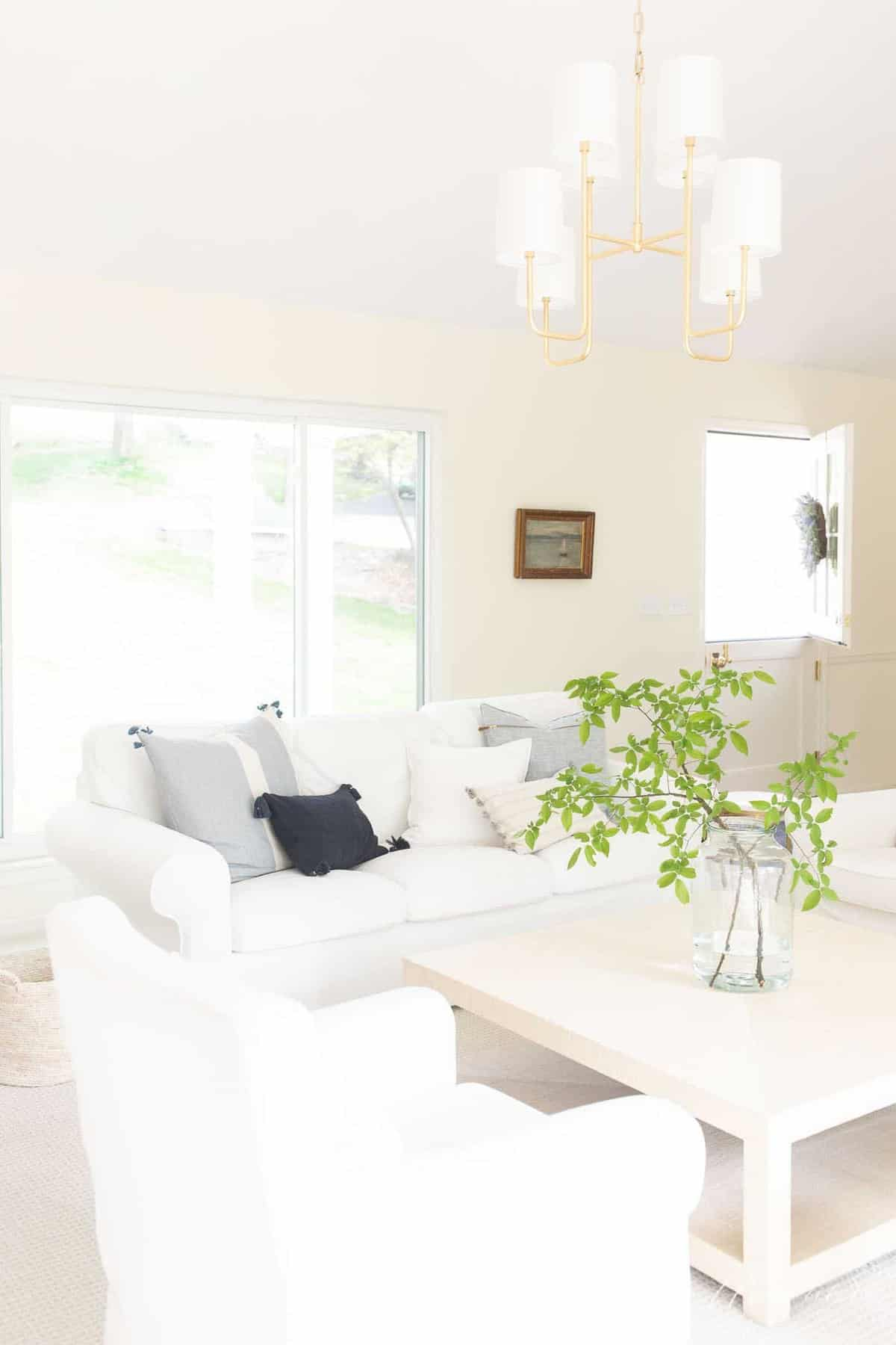 brass overhead lighitng in neutral room with white sofa and coffee table