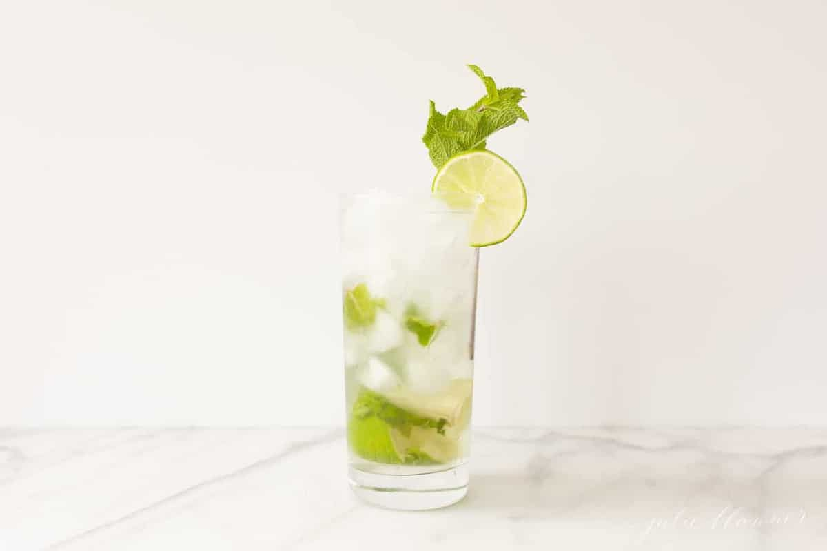 white countertop featuring a tall clear glass with a classic Cuban mojito. #easymojito #mojitoreceta