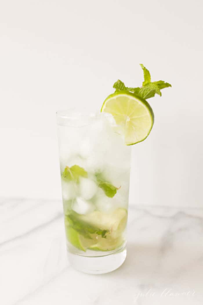 mojito in a tall glass with lime and mint