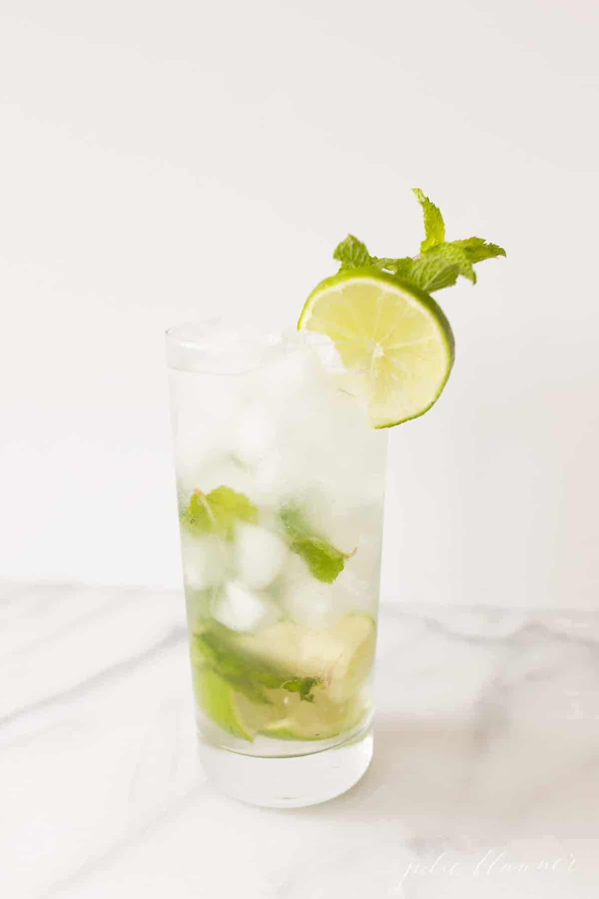 marble countertop with a tall slender glass of a fresh Cuban mojito.
