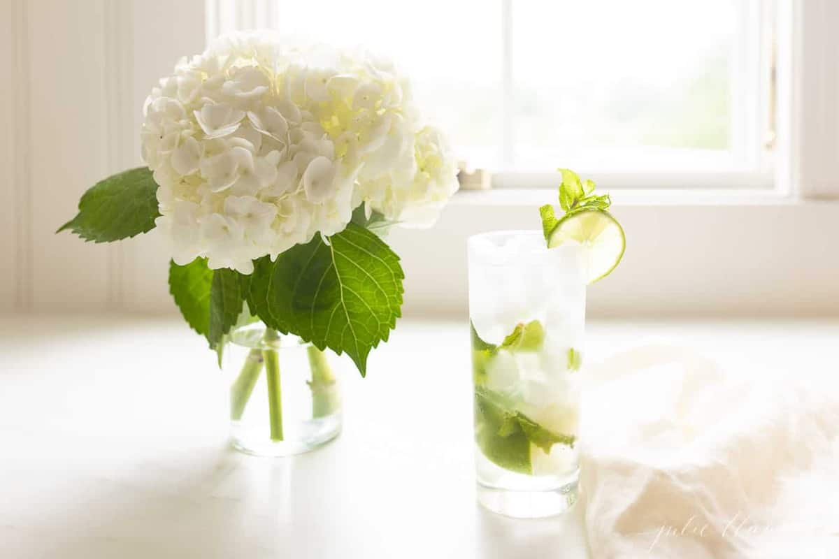 white countertop featuring a vase of hydrangea and a tall clear glass with a mojito. #easymojito #mojitoreceta