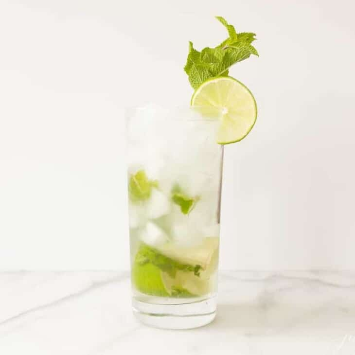 A classic mojito recipe in a clear glass on a marble surface, garnished with sprig of mint and a slice of lime.