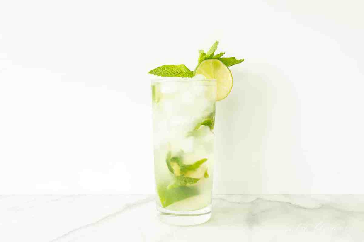 mojito recipe vodka in glass garnished with mint and lime slice on marble