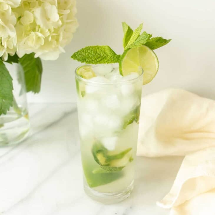 vodka mojito garnished with lime and mint by napkin and flowers