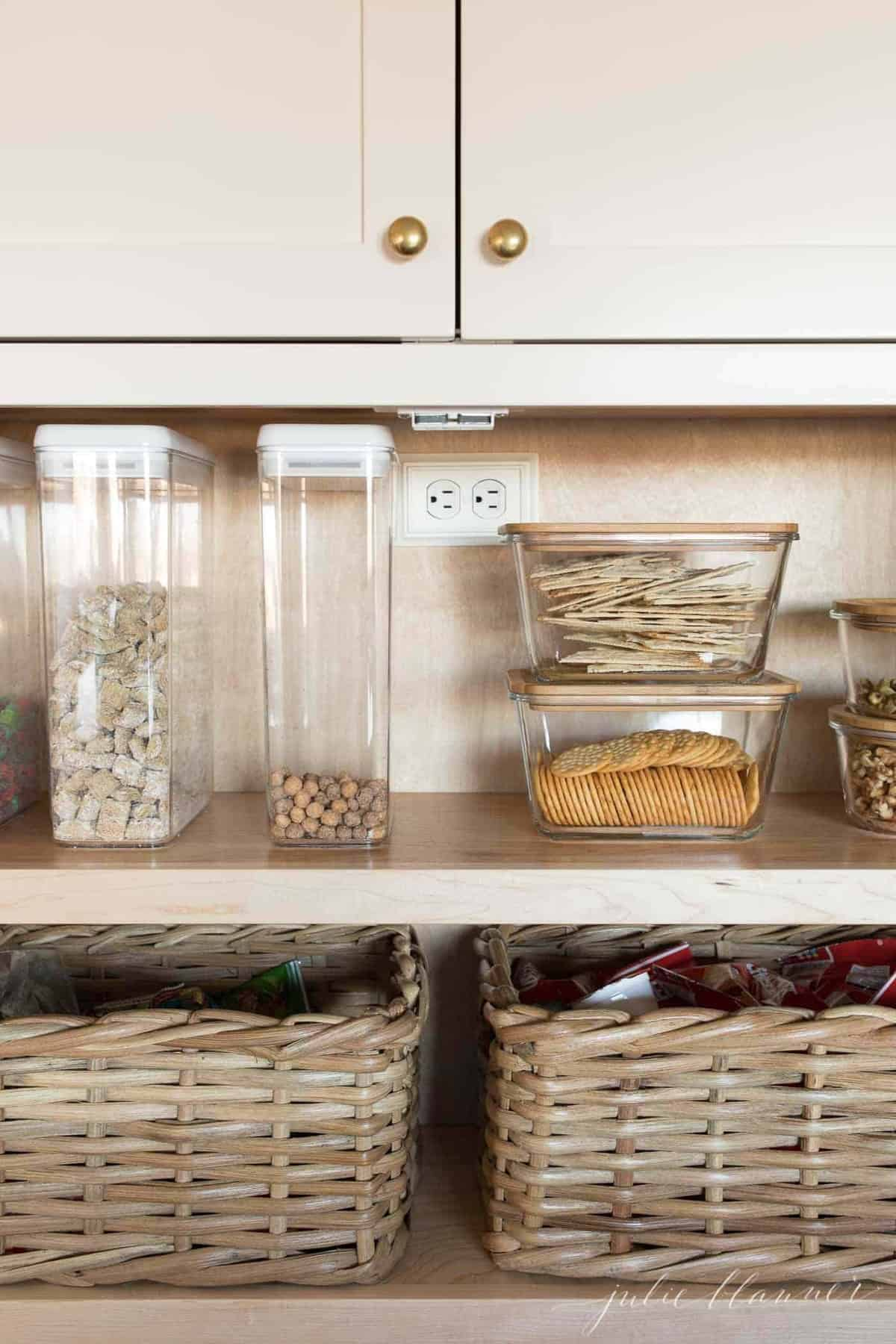 pantry organized with clear containers of snacks for back to school
