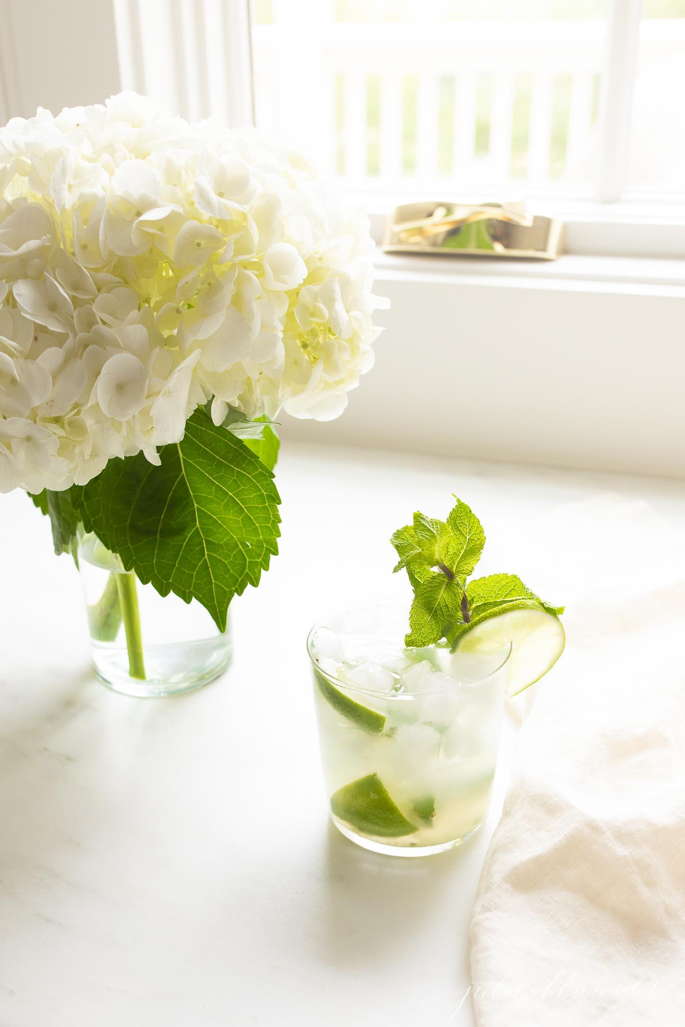 skinny mojito next to a vase of hydrangea