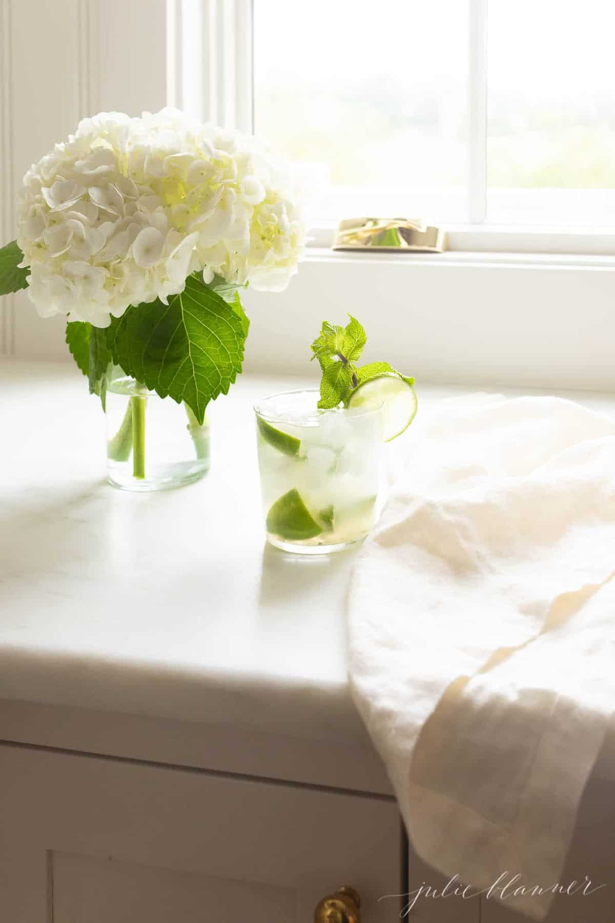 skinny mojito next to a linen napkin and vase of hydrangea