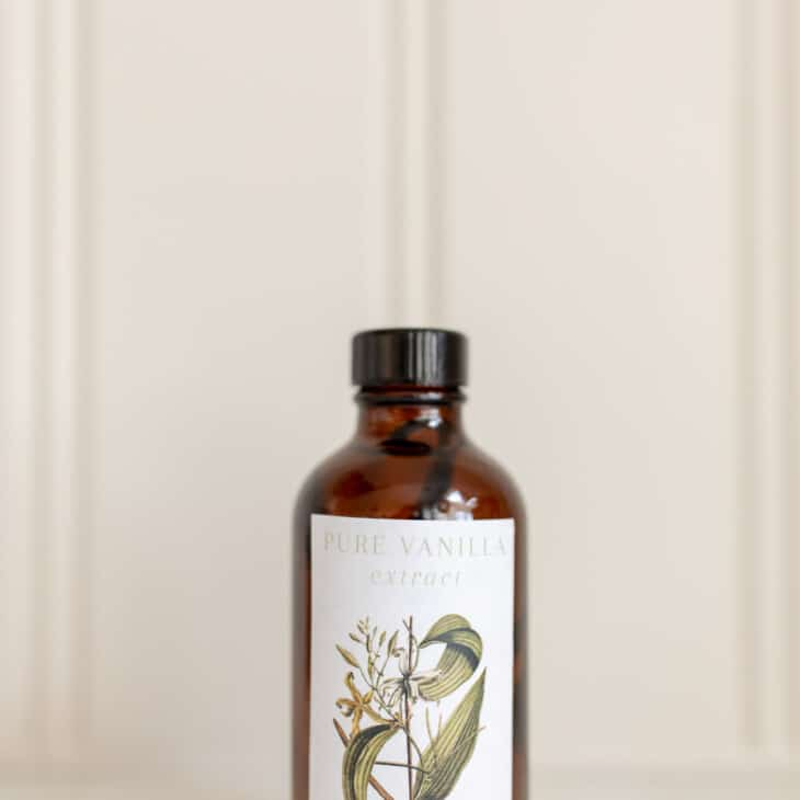 Amber bottle of homemade vanilla extract against a white countertop and background.