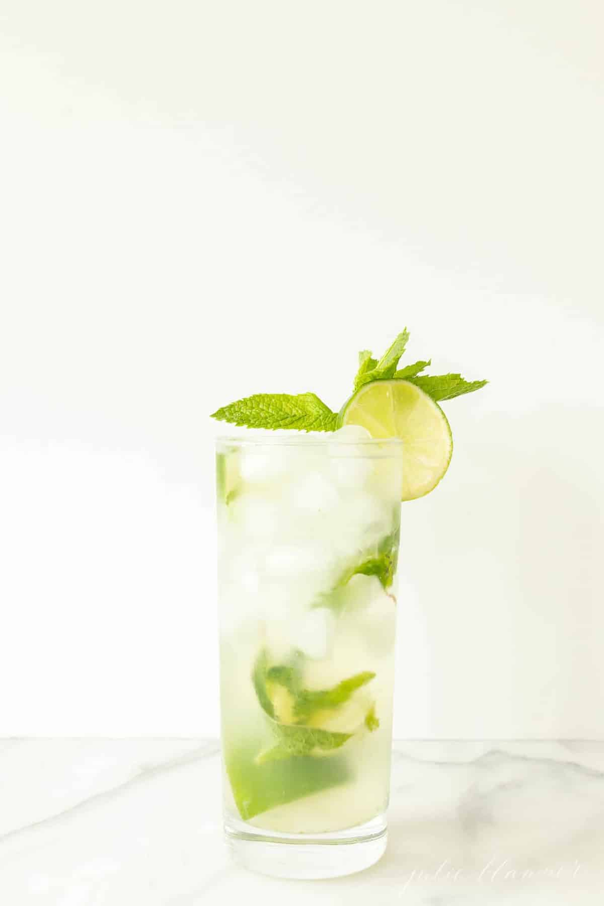 vodka mojito in a mojito glass garnished with lime slice and mint sprig