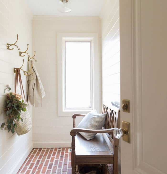 mudroom with brick floors, cream walls and white ceiling.