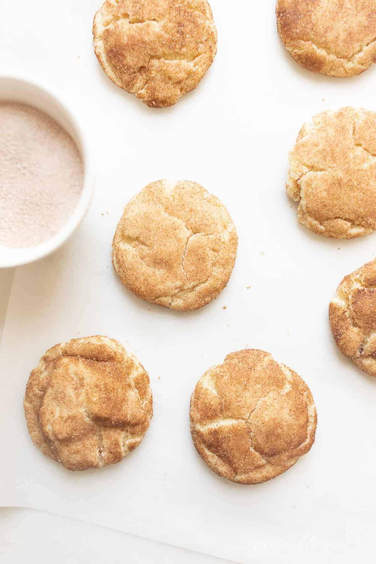 Soft and fluffy snickerdoodle cookies on a white countertop. #easysnickerdoodlecookierecipe #softsnickerdoodlerecipe
