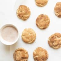 Soft and fluffy snickerdoodle cookies on a white countertop with a bowl of cinnamon and sugar. #easysnickerdoodlecookierecipe #softsnickerdoodlerecipe