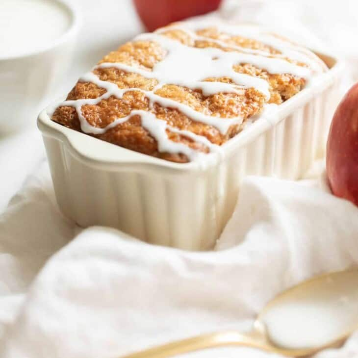 A small white ceramic loaf pan holding fresh baked apple cinnamon bread, drizzled with icing.