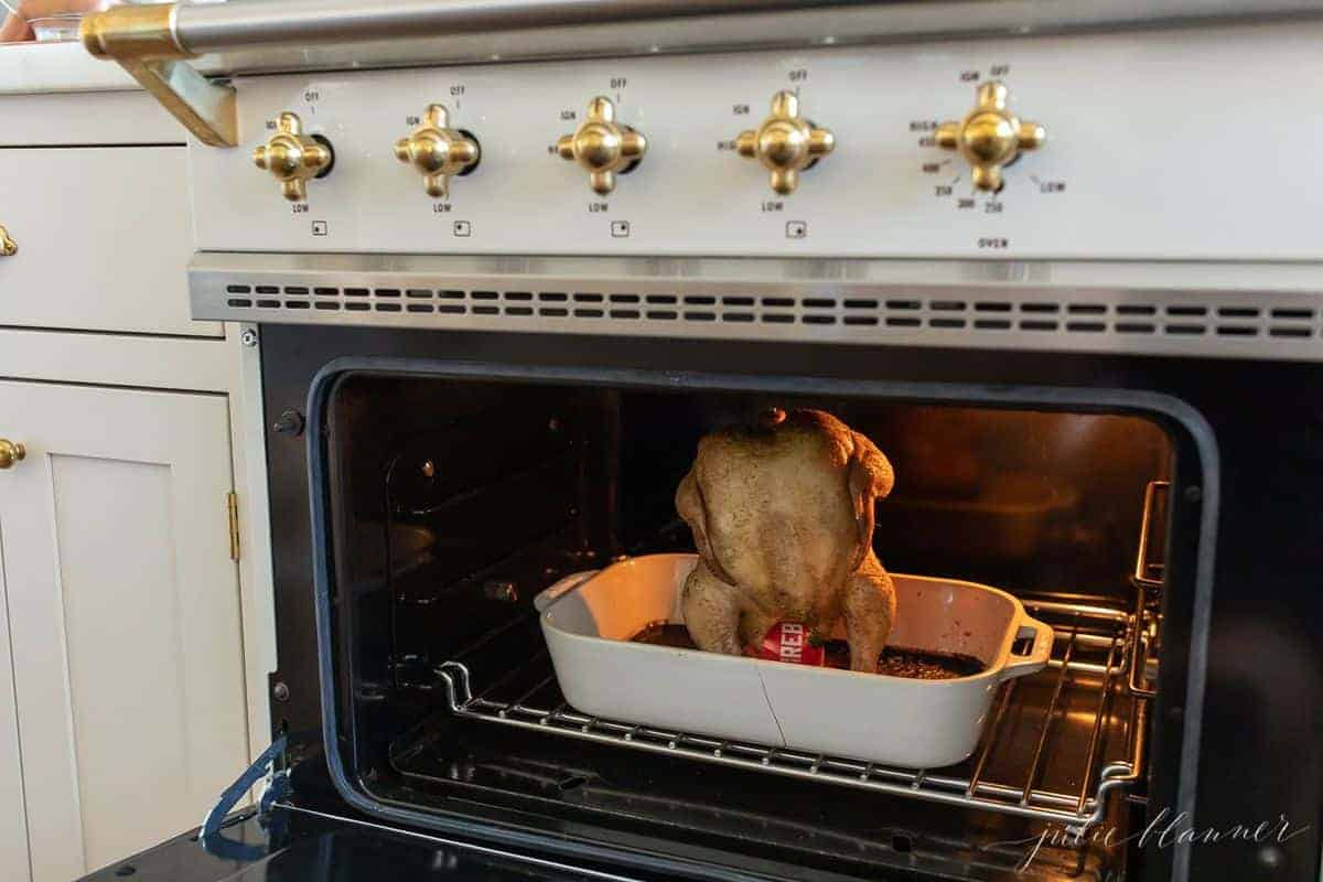 Looking inside range at a beer can chicken in the oven, inside a white roasting pan. #beerchicken #beercanchickeninoven