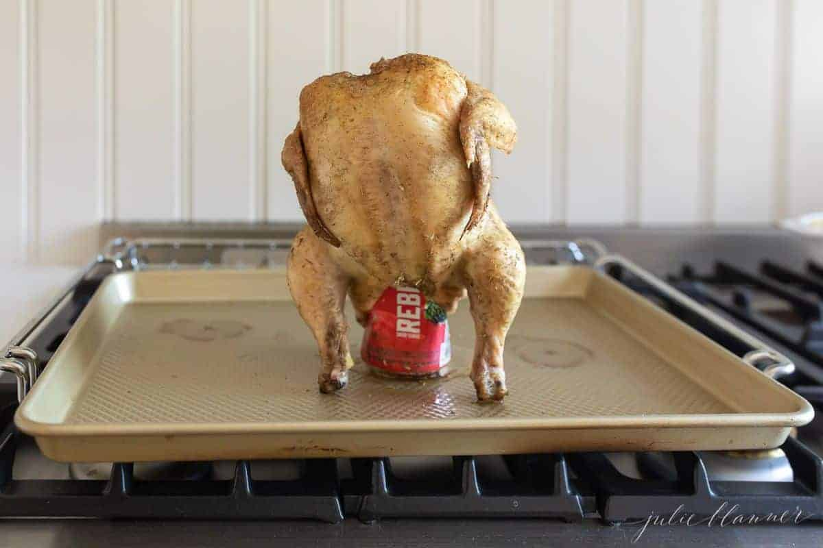 Whole chicken resting on a can of beer, on a gold sheetpan. #beercanchicken