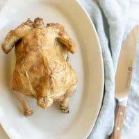 White platter featuring a beer can roasted chicken with golden skin. Blue linen napkin to side. #beercanchicken