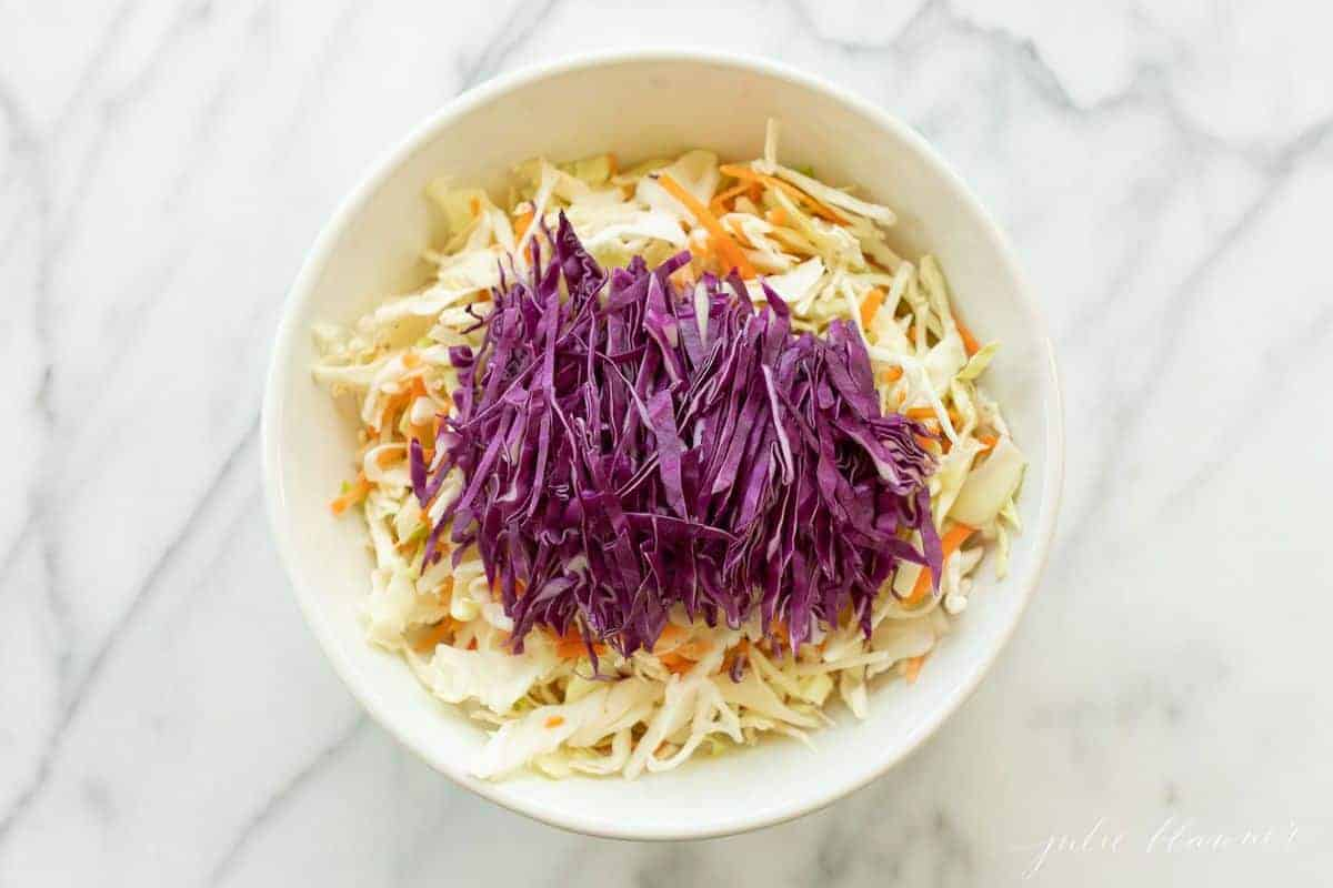 Puprple and orange coleslaw mix in a white bowl with a white marble counter in the background. #cabbagesalad