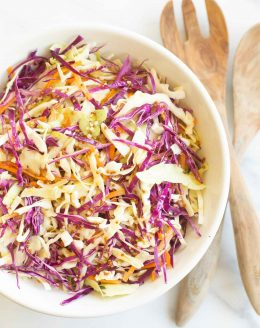 White salad bowl filled with colorful cabbage salad and wooden serving spoons. #cabbagesalad