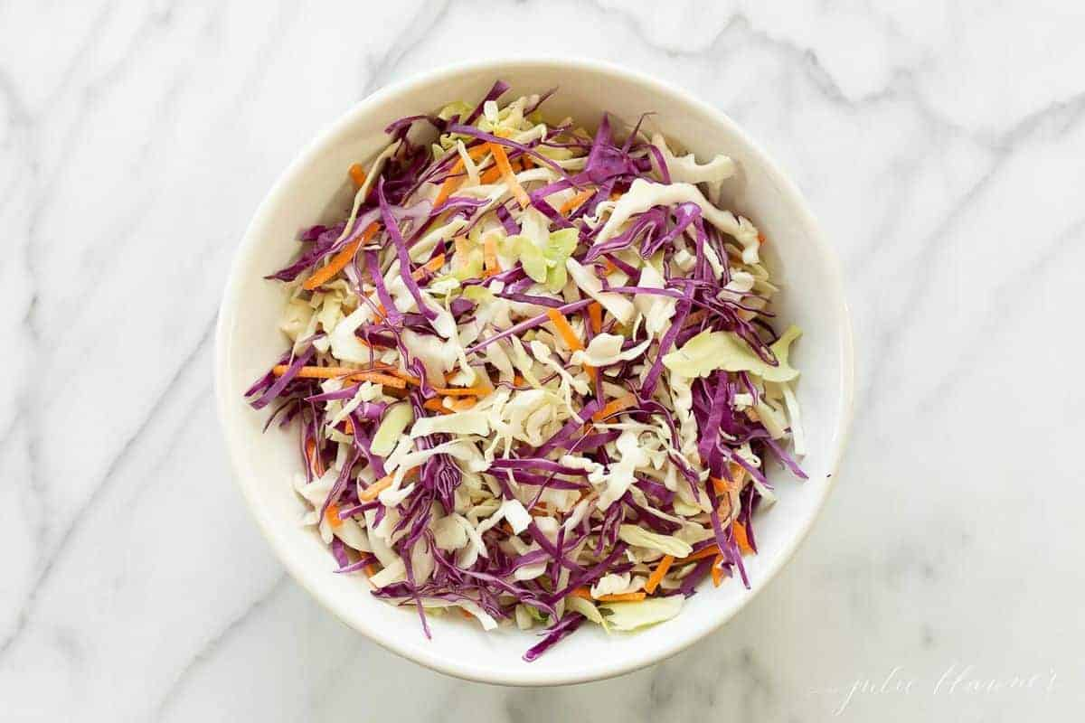 White salad bowl filled with colorful cabbage salad against a white marble counter top. #cabbagesalad