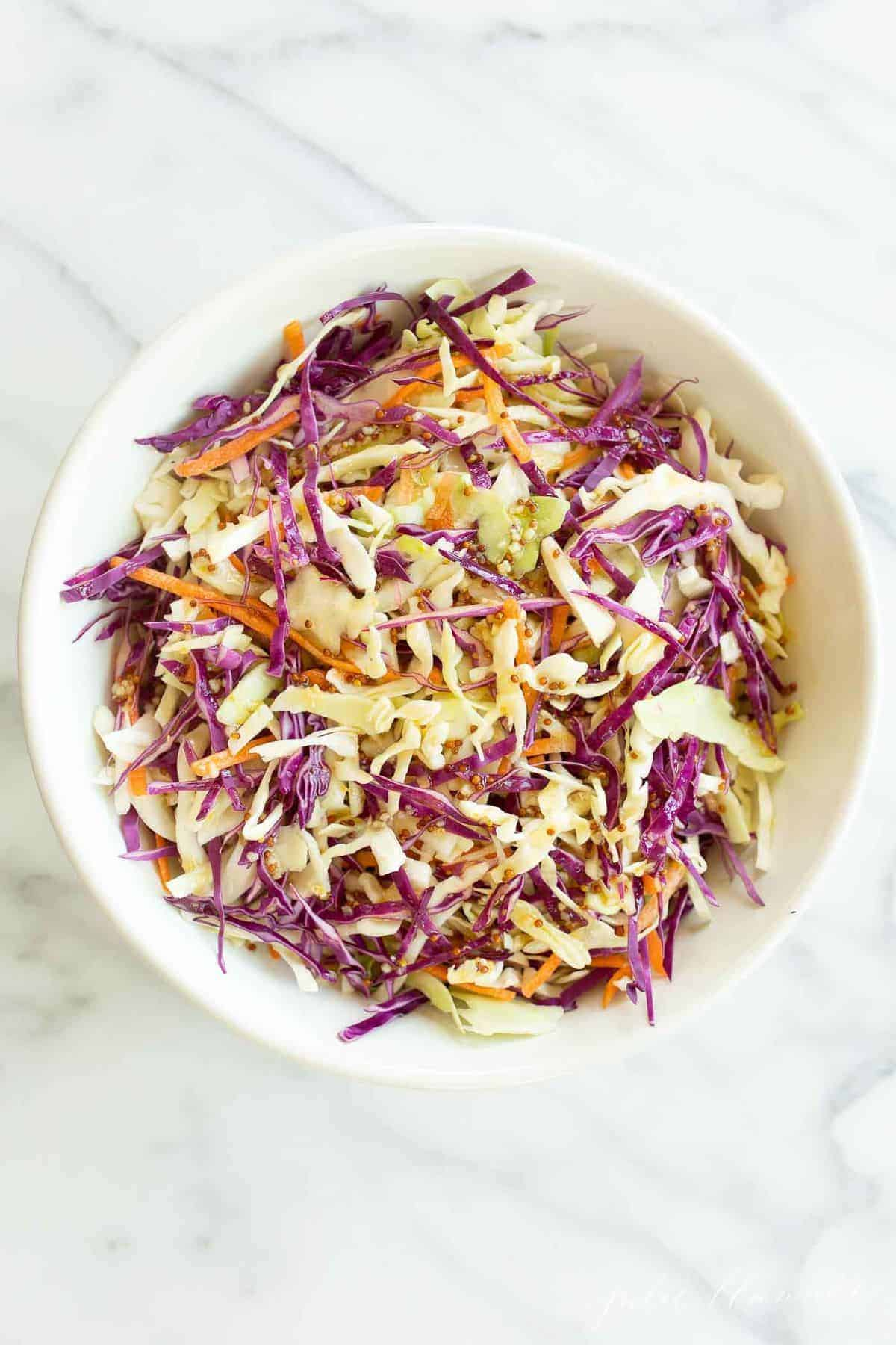 Colorful cabbage salad in a white bowl.