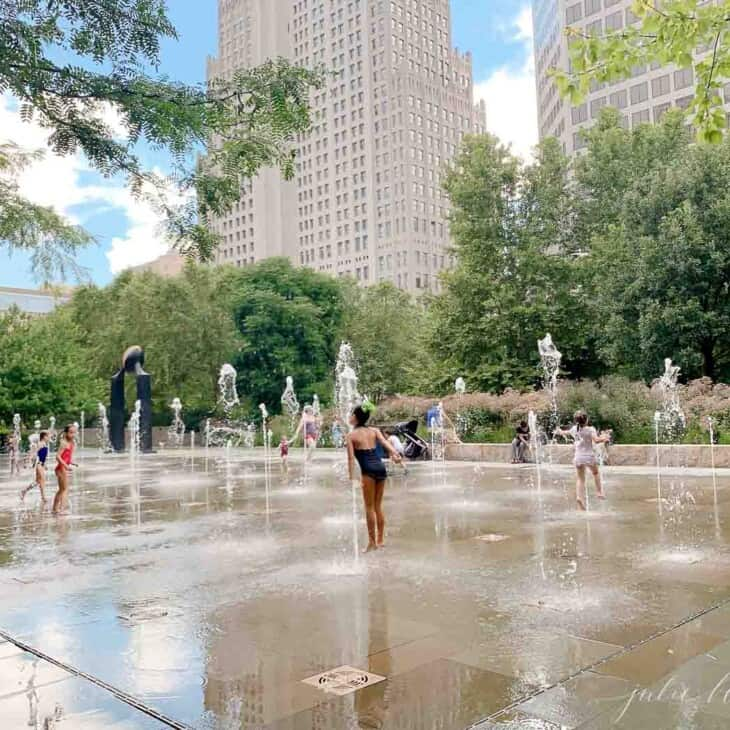 Concrete foundtain/ splash park with St. Louis high rise in background.