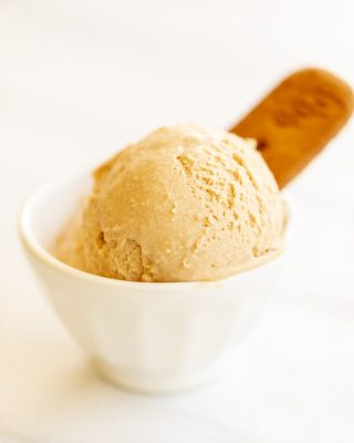 White bowl with two scoops of cookie butter ice cream, on a white surface. #cookiebuttericecream #speculoosicecream