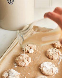 A glass jar pouring apple glaze onto cookies on a gold baking sheet. #appleglaze #appleciderglaze