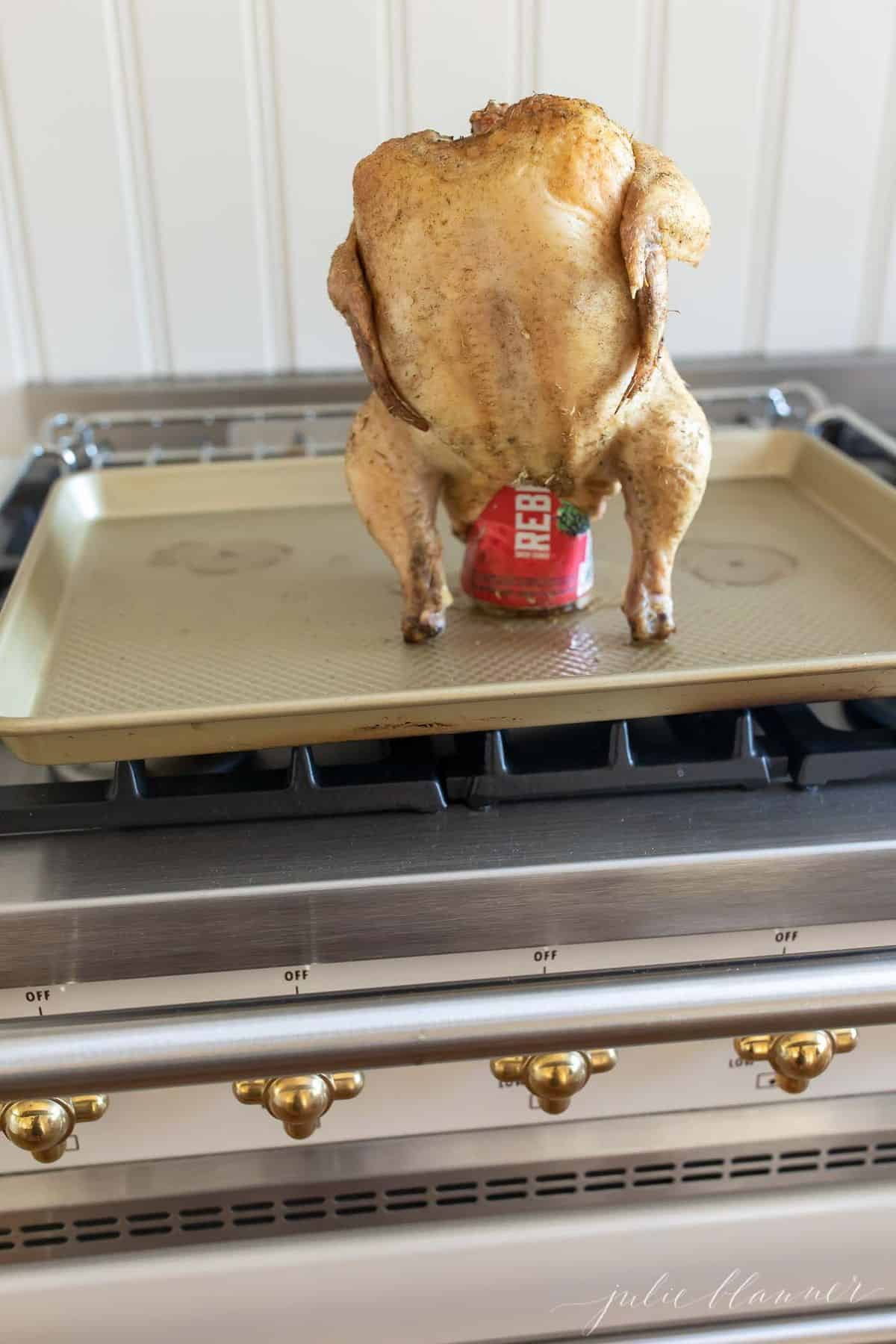 Verical image of roasted chicken resting on a beer can, placed on a gold sheetpan on top of range. #beercanchicken