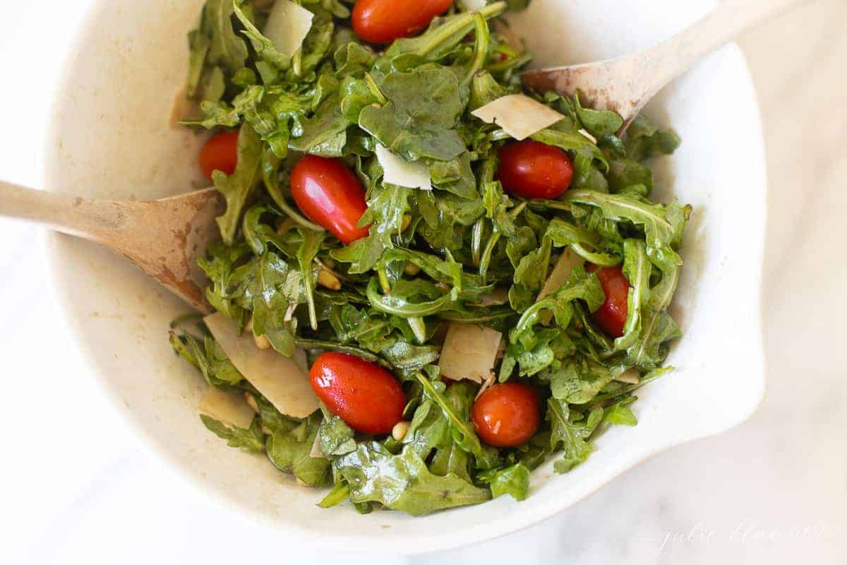 White salad bowl on a white counter with arugula and cherry tomatoes.