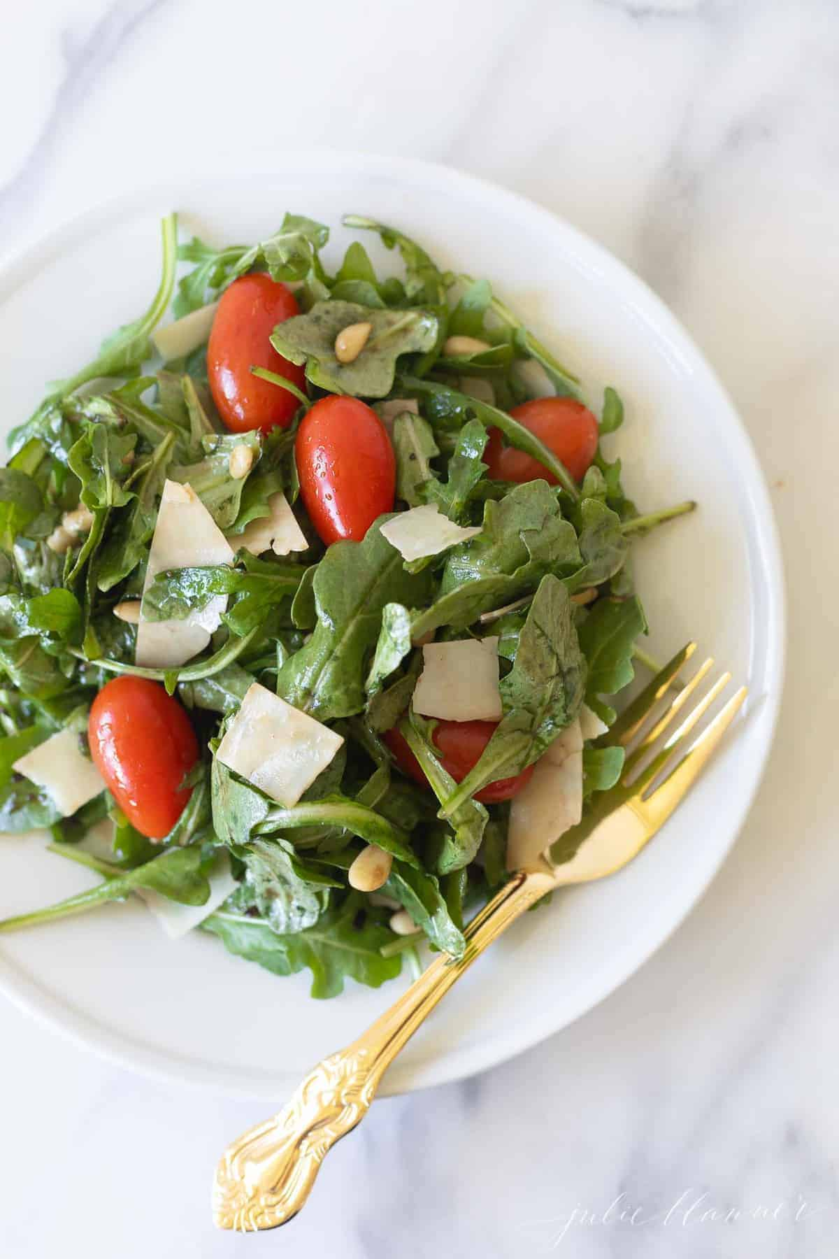 Marble countertop with a white salad plate filled with a green salad, cherry tomatoes, parmesan and more.