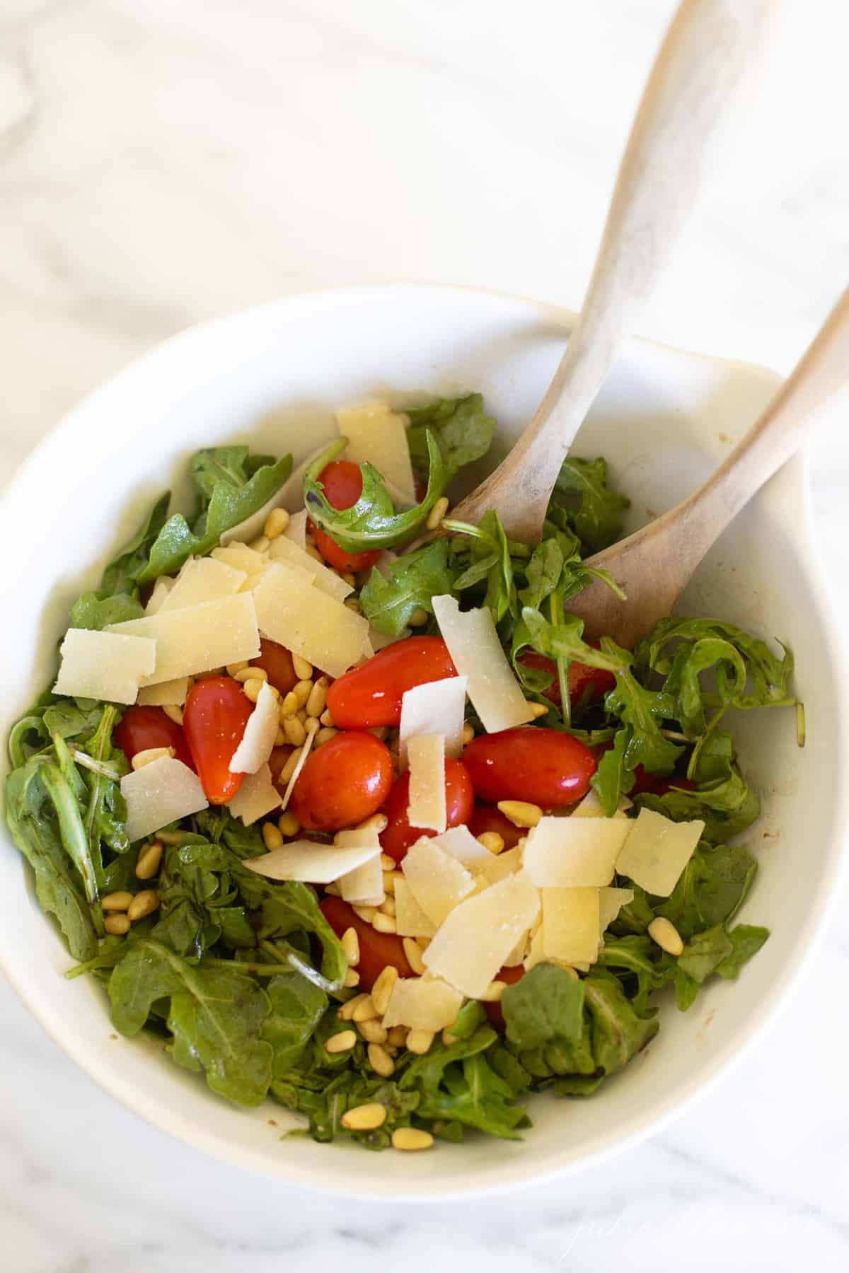 White salad bowl with bright arugula, cherry tomatoes and parmesan.