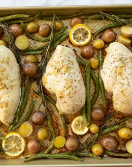 Gold sheetpan filled with baked chicken and veggies such as green beans, baby potatoes and lemon slices.