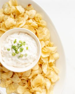 sour cream dip in a bowl surrounded by chips on a platter
