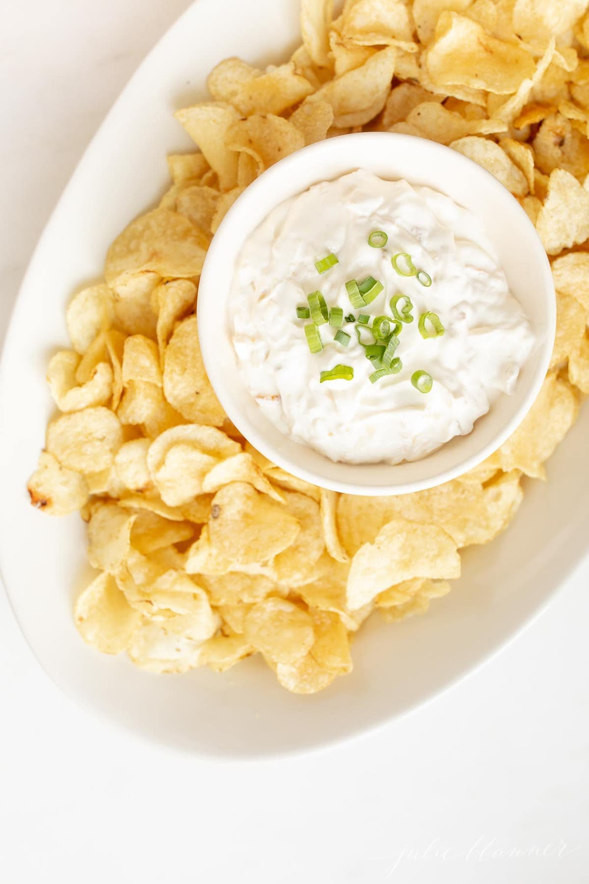 sour cream chip dip in a bowl on a platter with chips
