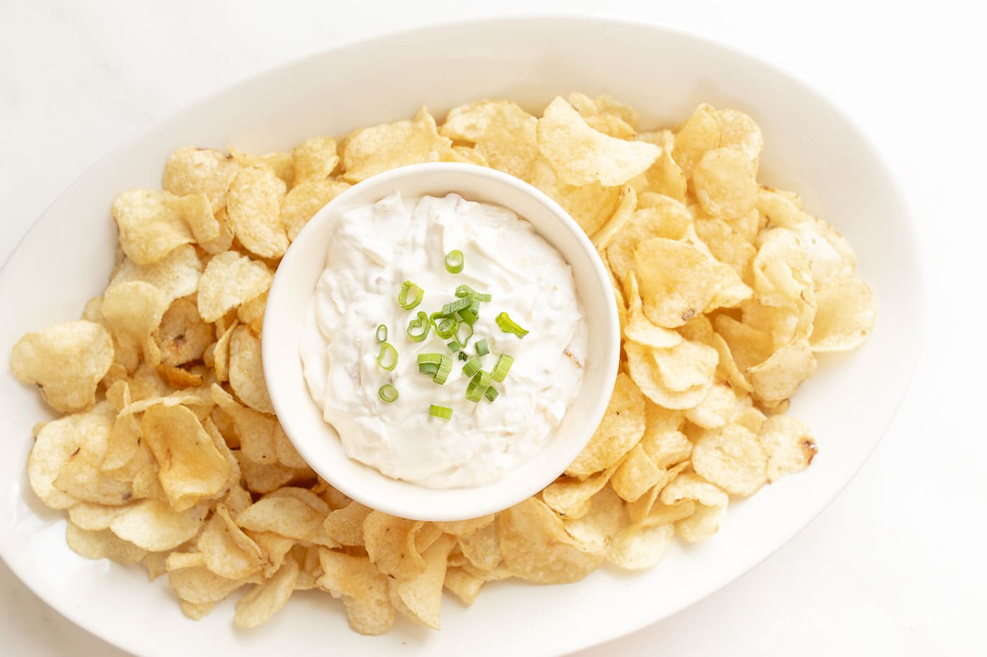 sour cream dip on a platter surrounded by chips