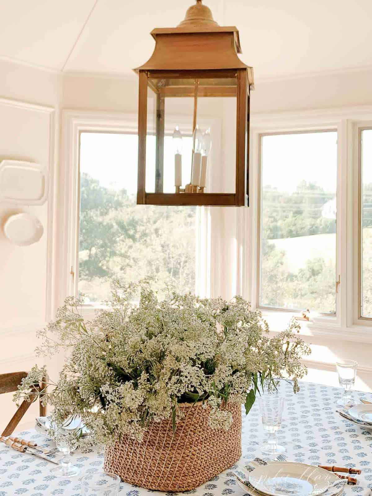 basket of wildflowers brass lantern and kalamkari block print table cloth