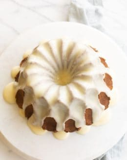 a bundt cake on a marble platter, covered in white glaze.