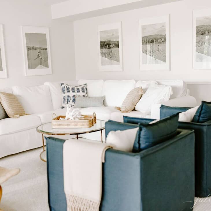 Living room scene with a white sectional, large photos on the wall and a wooden side table featuring a houseplant. #zzplant #zzplantcare