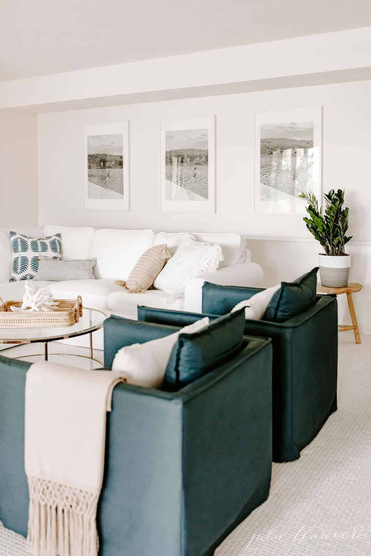 Living room scene with large photos on the wall and a wooden side table featuring a houseplant. #zzplant #zzplantcare