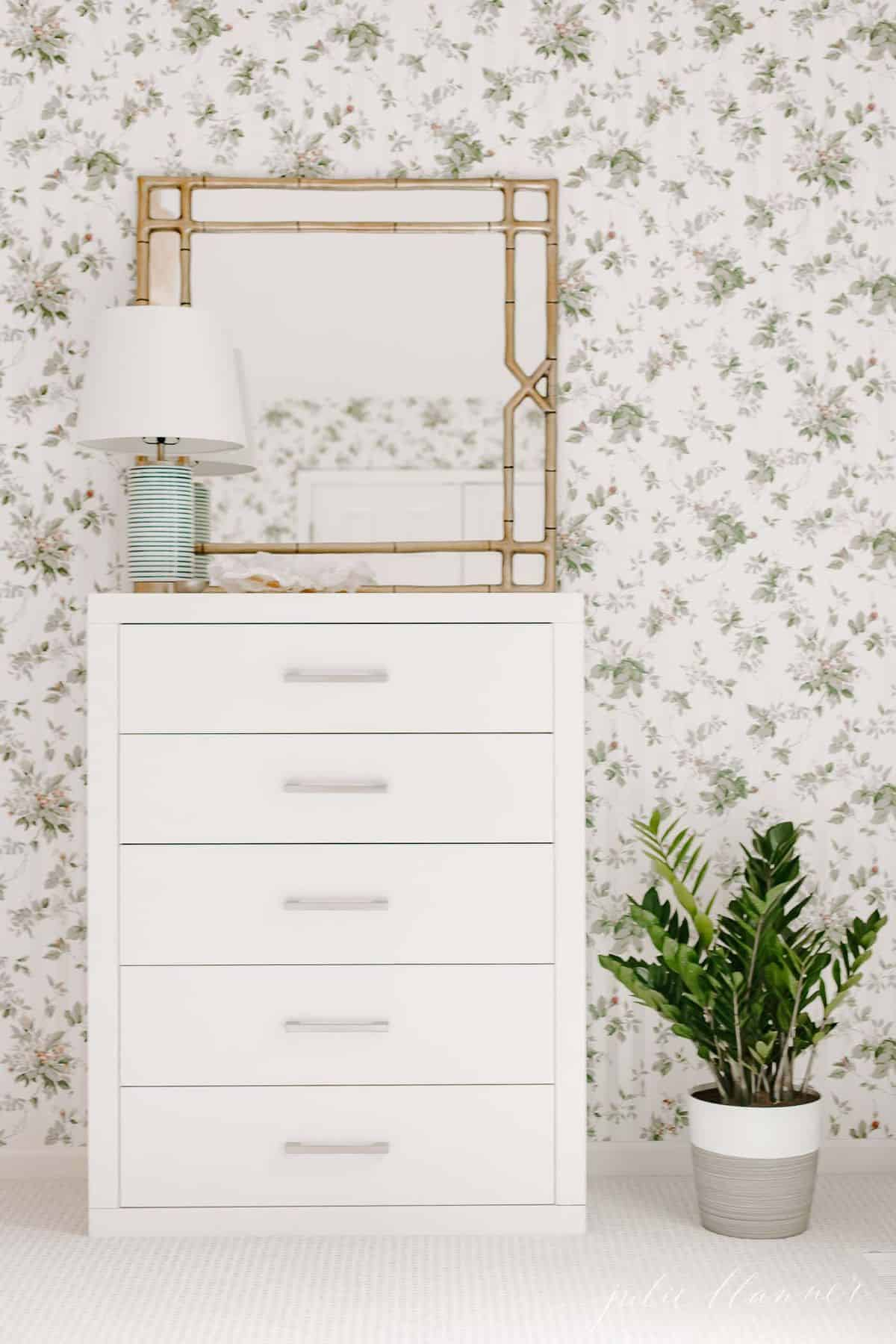 Floral wallpapered bedroom, with a modern white dresser and gold mirror, Zamioculcas Zamiifolia on the floor beside dresser