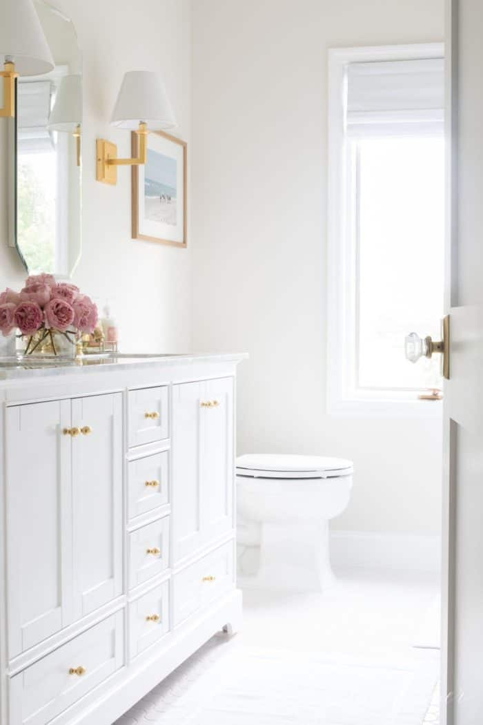 Peaking into a white bathroom past a door that's ajar. #spatub #airtub #showerniche