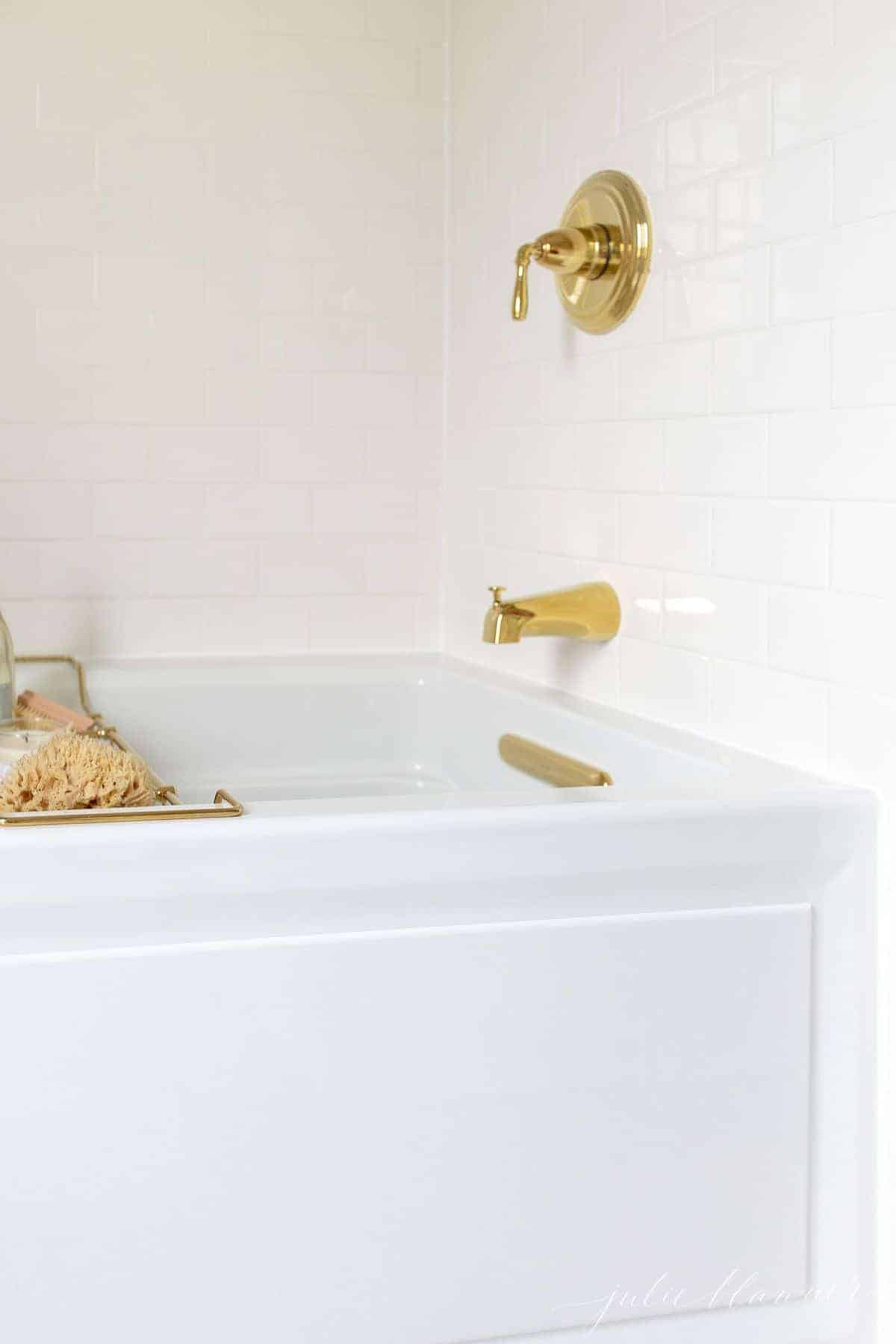 Air tub with brass bath fittings and a brass bath tray filled with relaxing spa treatments.