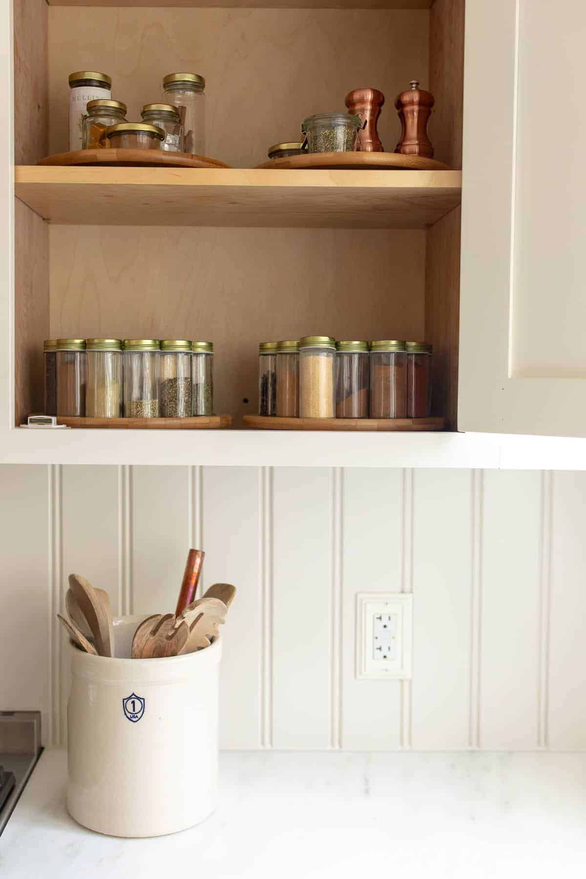 Simple cream kitchen with one cabinet open, clear glass spice jars on lazy susan inside.