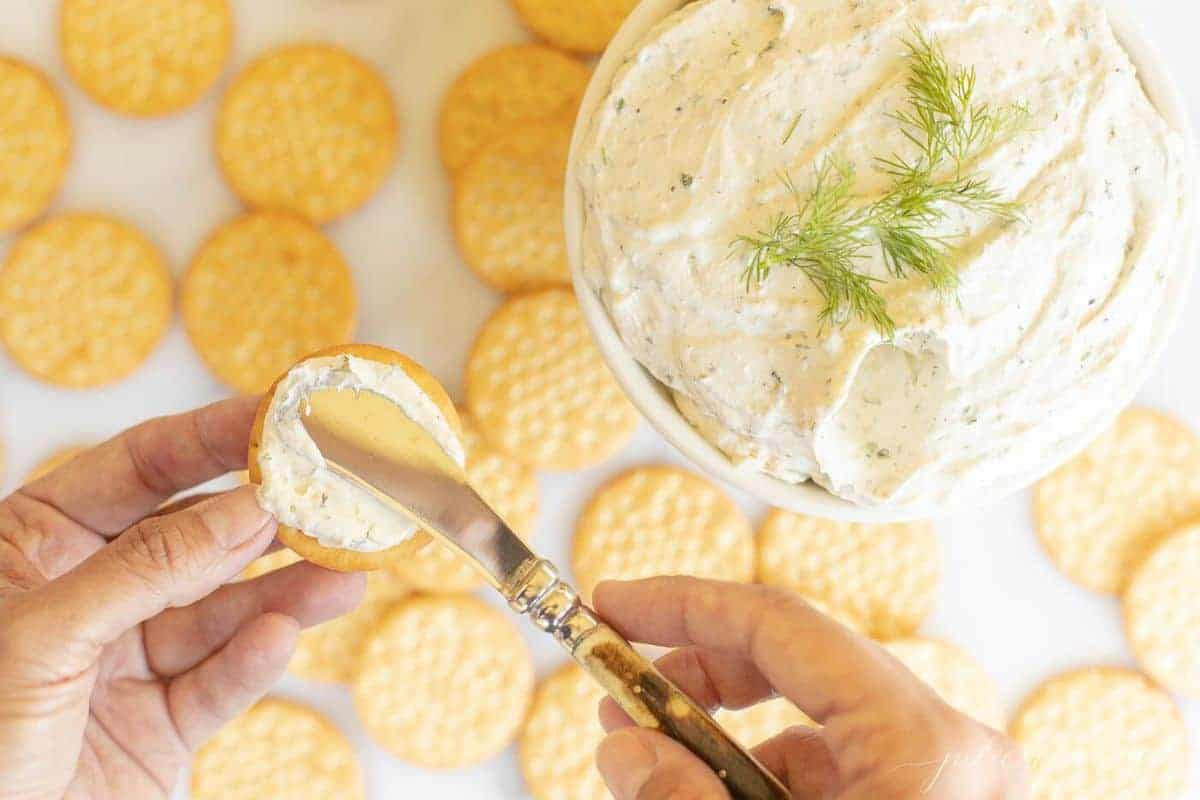 White bowl of herb cream cheese with crackers, and a hand spreading cheese onto a cracker. #homemadeboursin