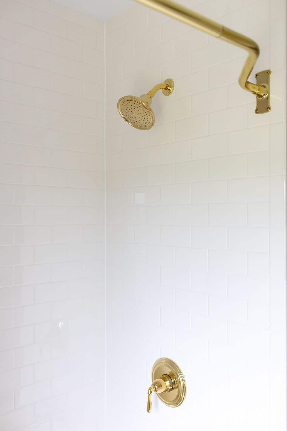 White subway til shower with brass showerhead and bathtub fixtures. #spatub #airbath #airtub