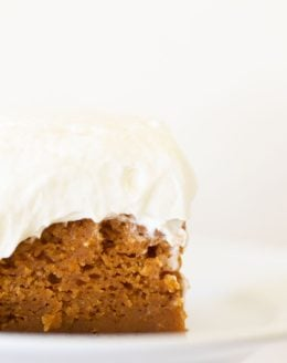 Close-up of a white plate with pumpkin cake covered in thick cream cheese frosting. #creamcheesefrostingrecipe